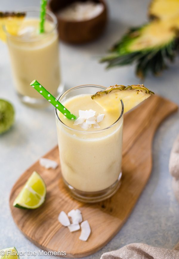 angled front view of pina colada smoothie with coconut flakes on top