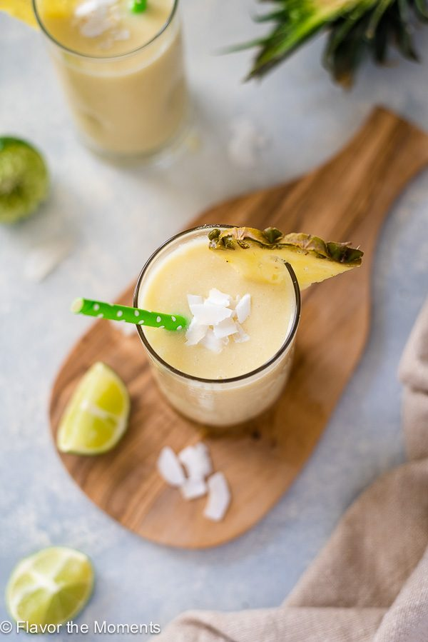 pina colada smoothie with green straw, pineapple slice and coconut flakes on top