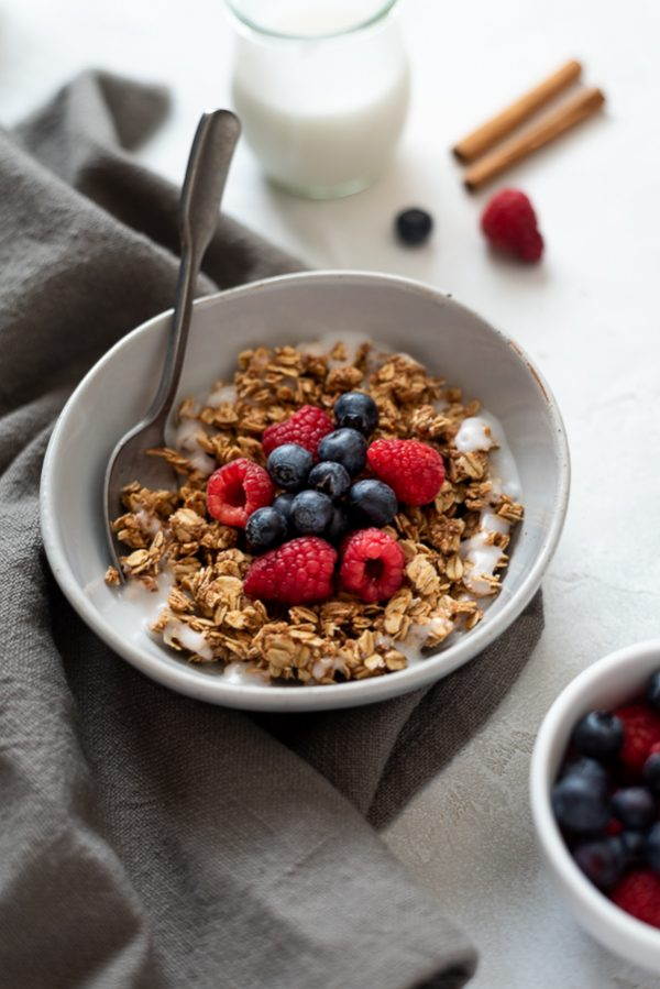 almond butter granola in a bowl topped with berries