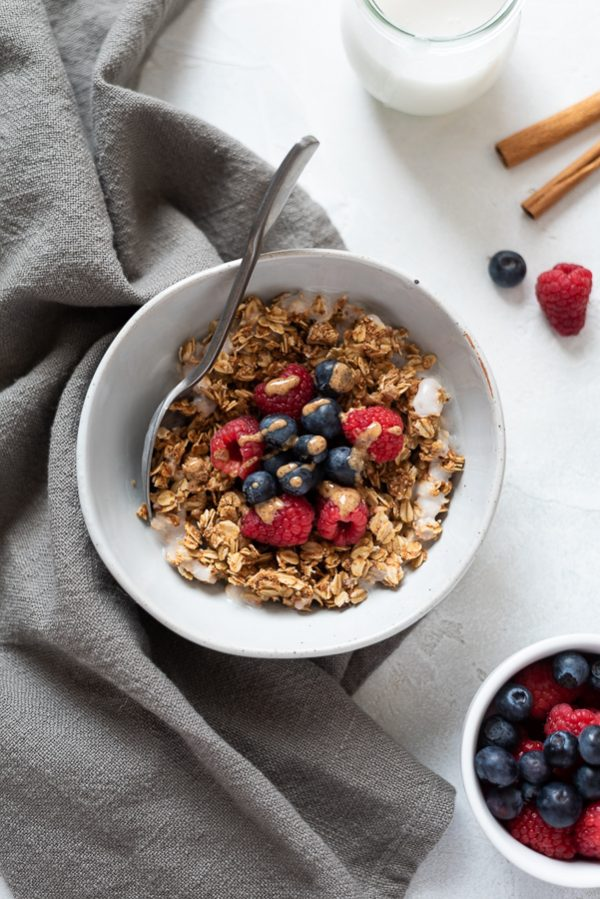 overhead shot of almond butter granola topped with berries and almond butter drizzle