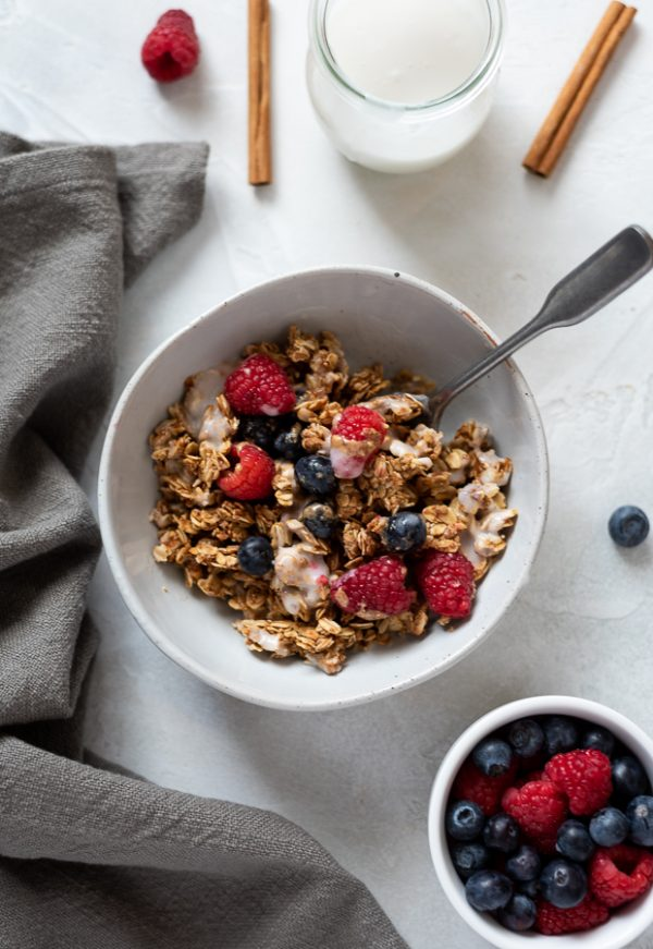 almond butter granola in bowl stirred up with berries and milk