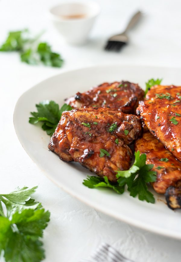 front view of grilled bbq chicken thigh on a platter