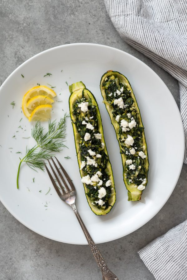 overhead shot of spanakopita stuffed zucchini boats on white plate with lemon and dill