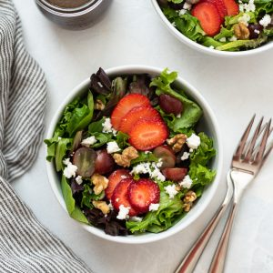 Strawberry salad in white bowl with two forks and linen alongside