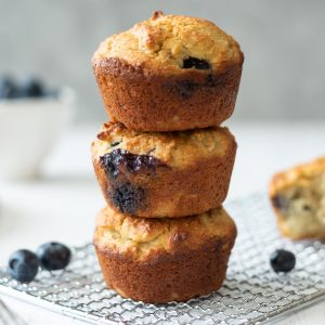 Three almond flour blueberry muffins stacked on a wire rack