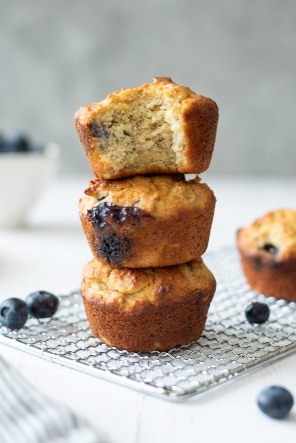 stack of almond flour blueberry muffins with a bite out of top muffin
