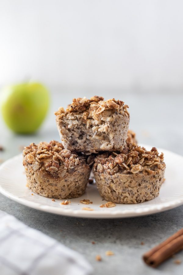 apple crisp baked oatmeal cups on a white plate with a bite out of one