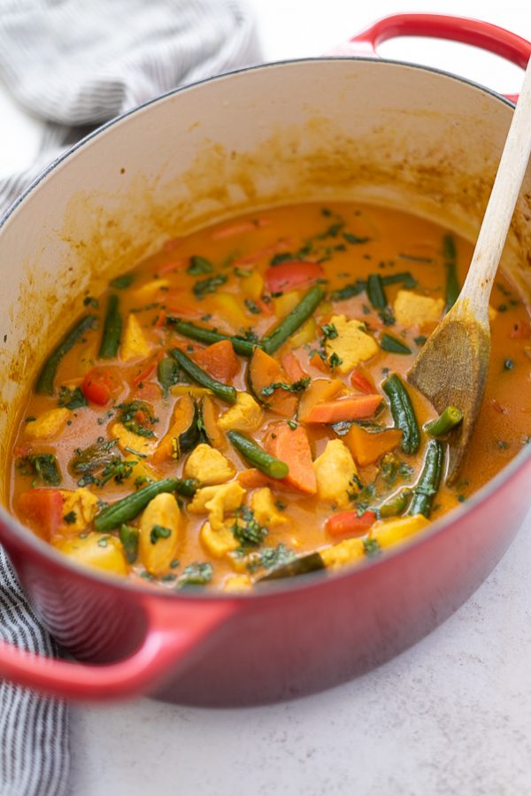 pumpkin curry in dutch oven with wooden spoon