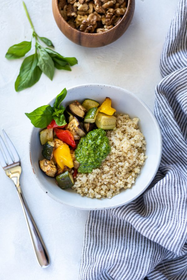 Roasted vegetable pesto quinoa bowl in bowl with basil