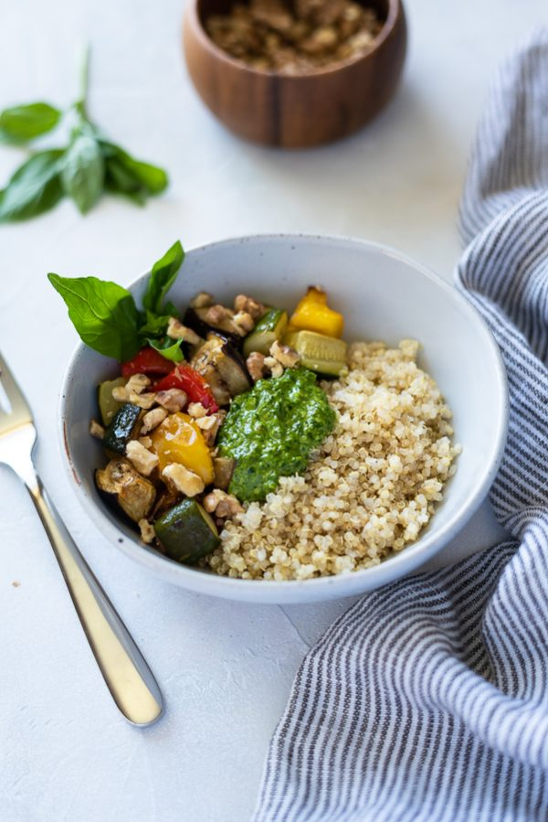 angled overhead shot of pesto quinoa bowls with roasted vegetables