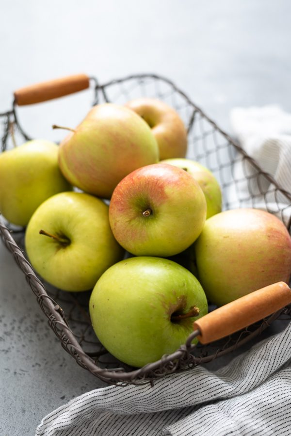 close up of apples in a wire basket