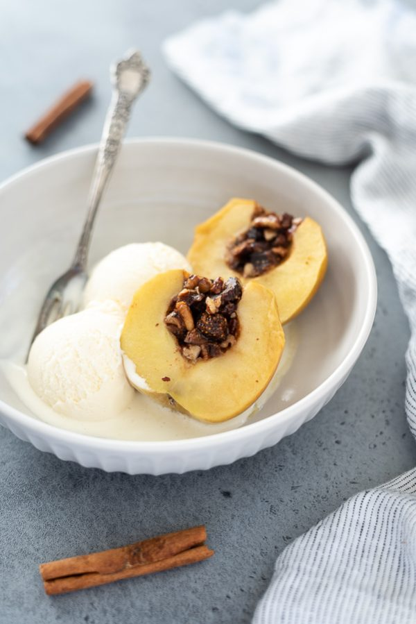 front shot of baked apples sliced in half in a bowl with ice cream