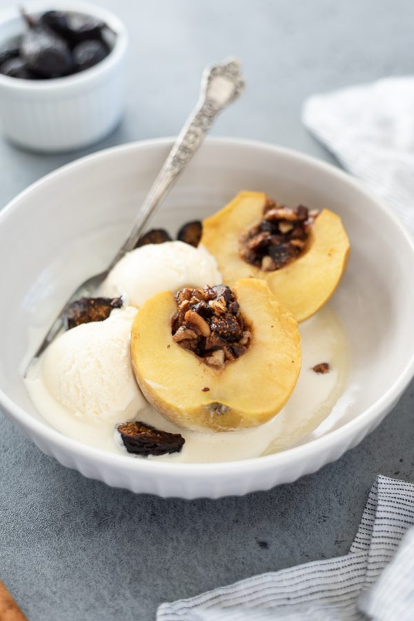 front shot of baked apples in a bowl with ice cream and dried figs
