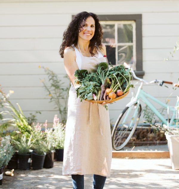 Marcie holding basket of vegetables