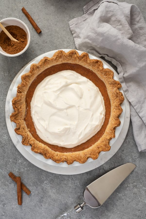 overhead shot of pumpkin pie from scratch topped with whipped cream