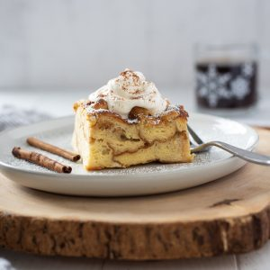 Eggnog french toast casserole on white plate topped with whipped cream
