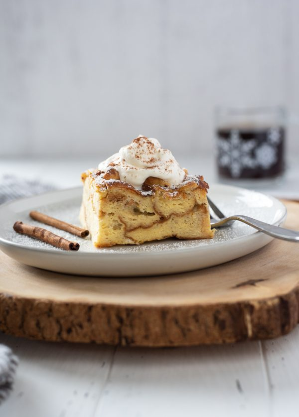 Eggnog french toast casserole with whipped cream on a plate