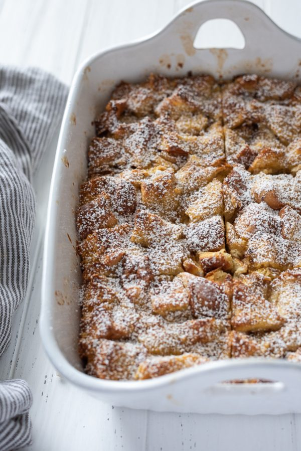 front shot of eggnog french toast casserole in baking dish topped with powdered sugar