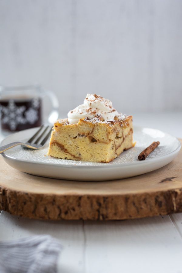 front shot of slice of eggnog french toast casserole on white plate with whipped cream