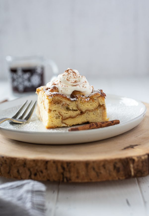 front shot of eggnog french toast casserole topped with whipped cream with fork alongside