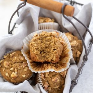 Healthy banana muffins in basket with bite out of top muffin