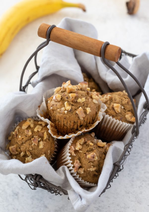 Flourless banana muffins in wire basket with paper liner unwrapped on top muffin