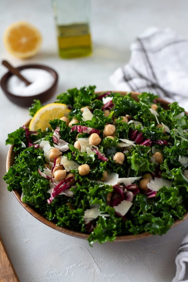 Massaged kale salad with chickpeas and parmesan in bowl -- front angled overhead shot