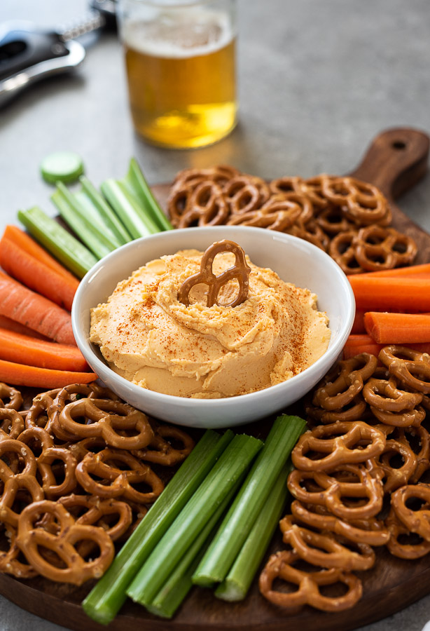 Pub cheese dip in a bowl surrounded by pretzels and vegetables