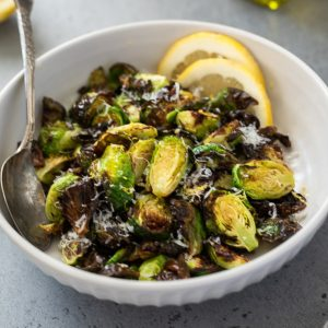 air fryer brussels sprouts in white bowl with lemon slices and spoon