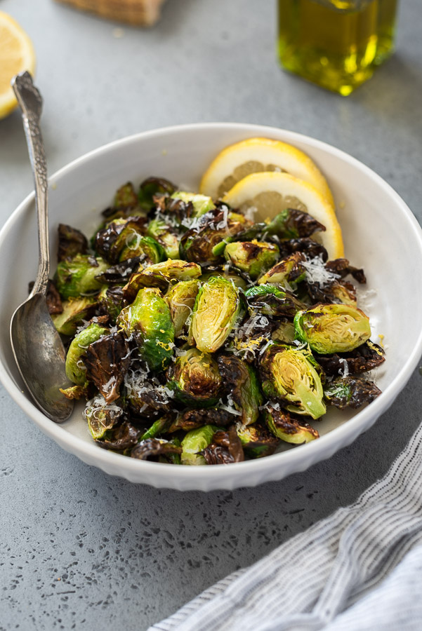 angled overhead shot of air fried brussels sprouts in serving bowl with spoon and linen alongside