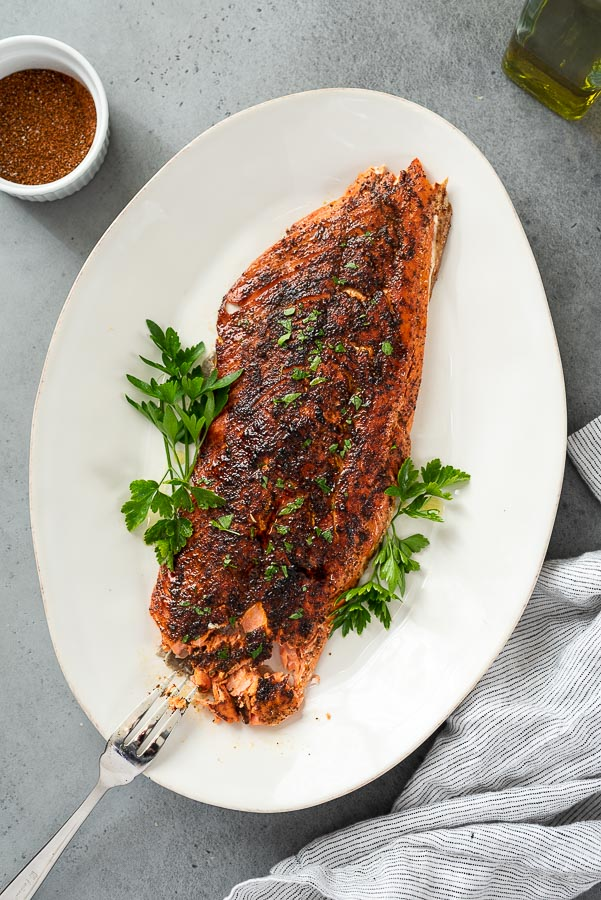 overhead shot of broiled salmon fillet on a white serving platter with fork flaking the fish