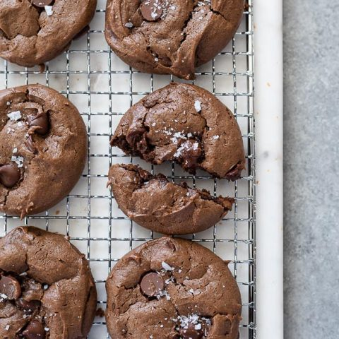 chocolate peanut butter cookies on a wire rack with close up on one split in half