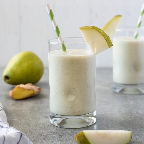 Pear smoothie in glass with striped straw and slice of pear