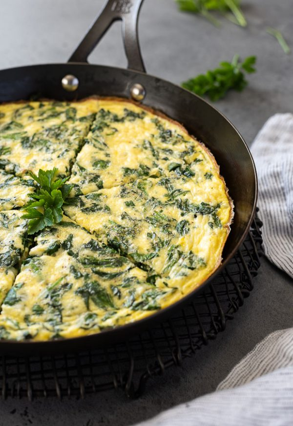 front close up shot of spinach and feta frittata sliced in cast iron skillet