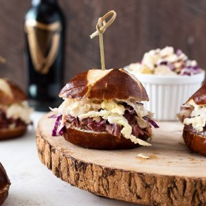 Guinness corned beef sliders with wooden pick through top.