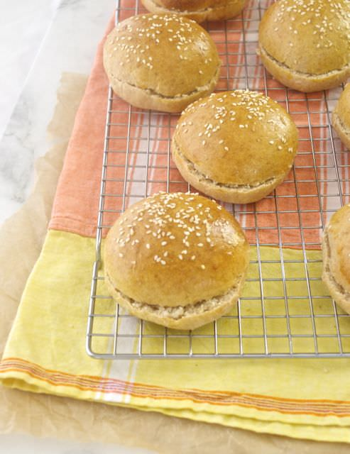 Homemade burger buns on a wire rack with linen underneath