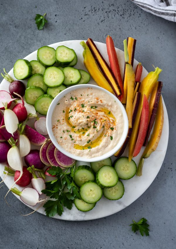 overhead shot of white bean hummus on a serving platter with vegetables