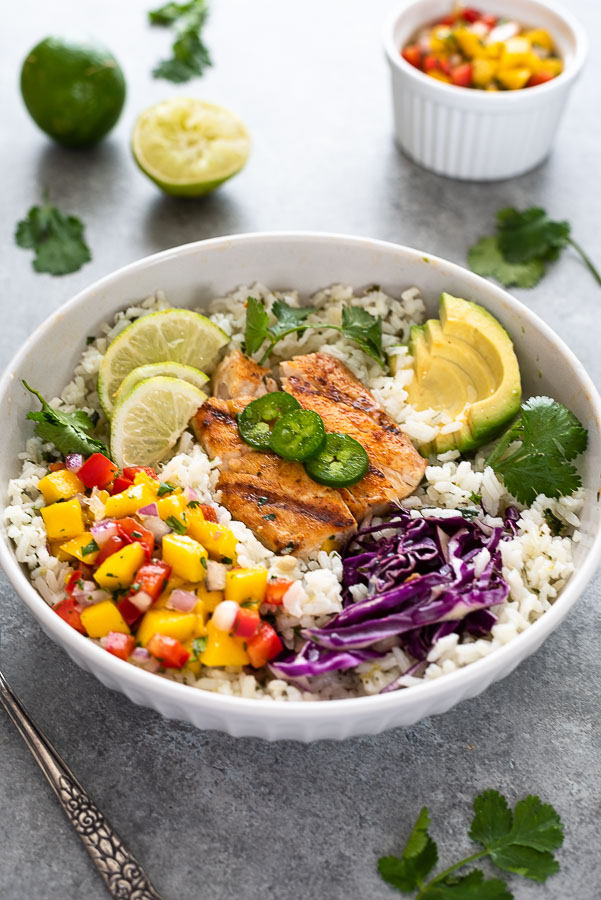 angled overhead shot of fish taco bowl over rice with toppings