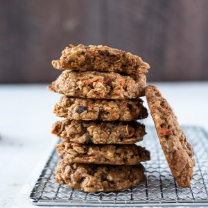 tall stack of healthy carrot oatmeal cookies with one cookie leaning against them