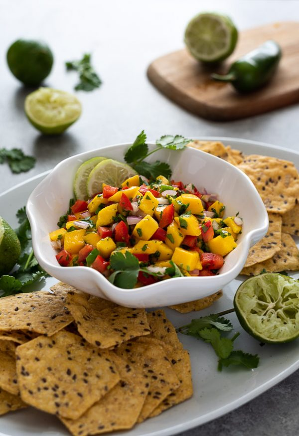 mango salsa in white bowl on platter with chips and lime
