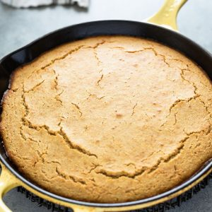 skillet cornbread in cast iron skillet with linen behind