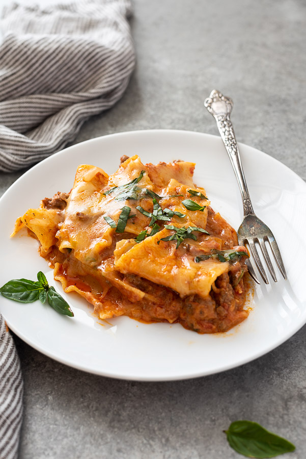 close up of one pot lasagna on a plate with fork alongside