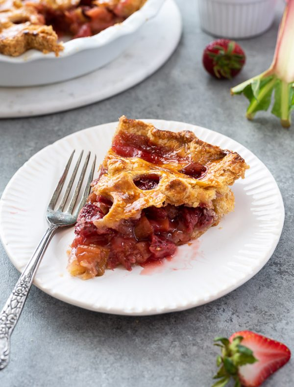 slice of strawberry rhubarb pie on a plate with fork alongside