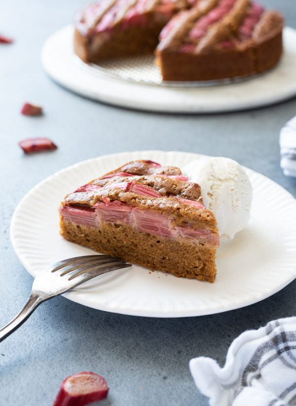 Slice of rhubarb cake on a plate with ice cream