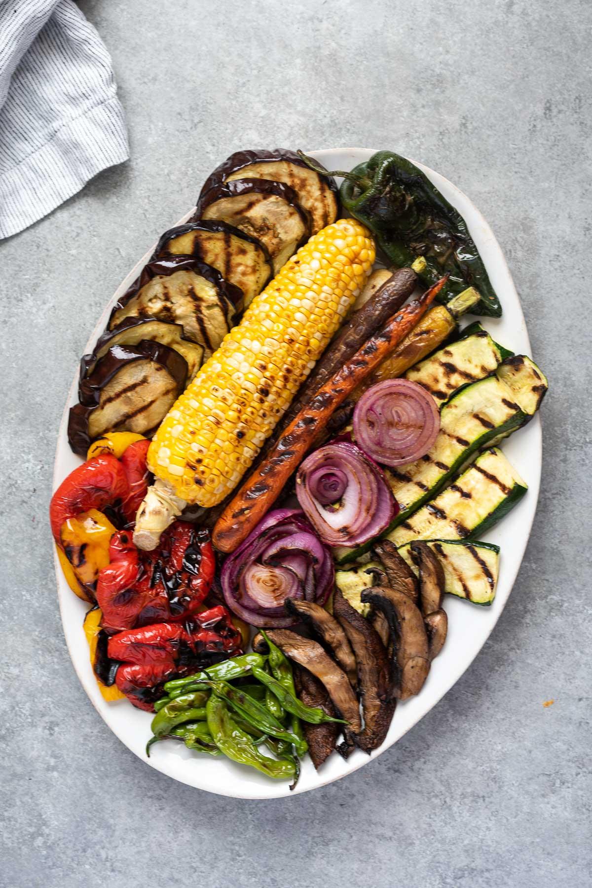 Grilled vegetables arranged on a white serving platter