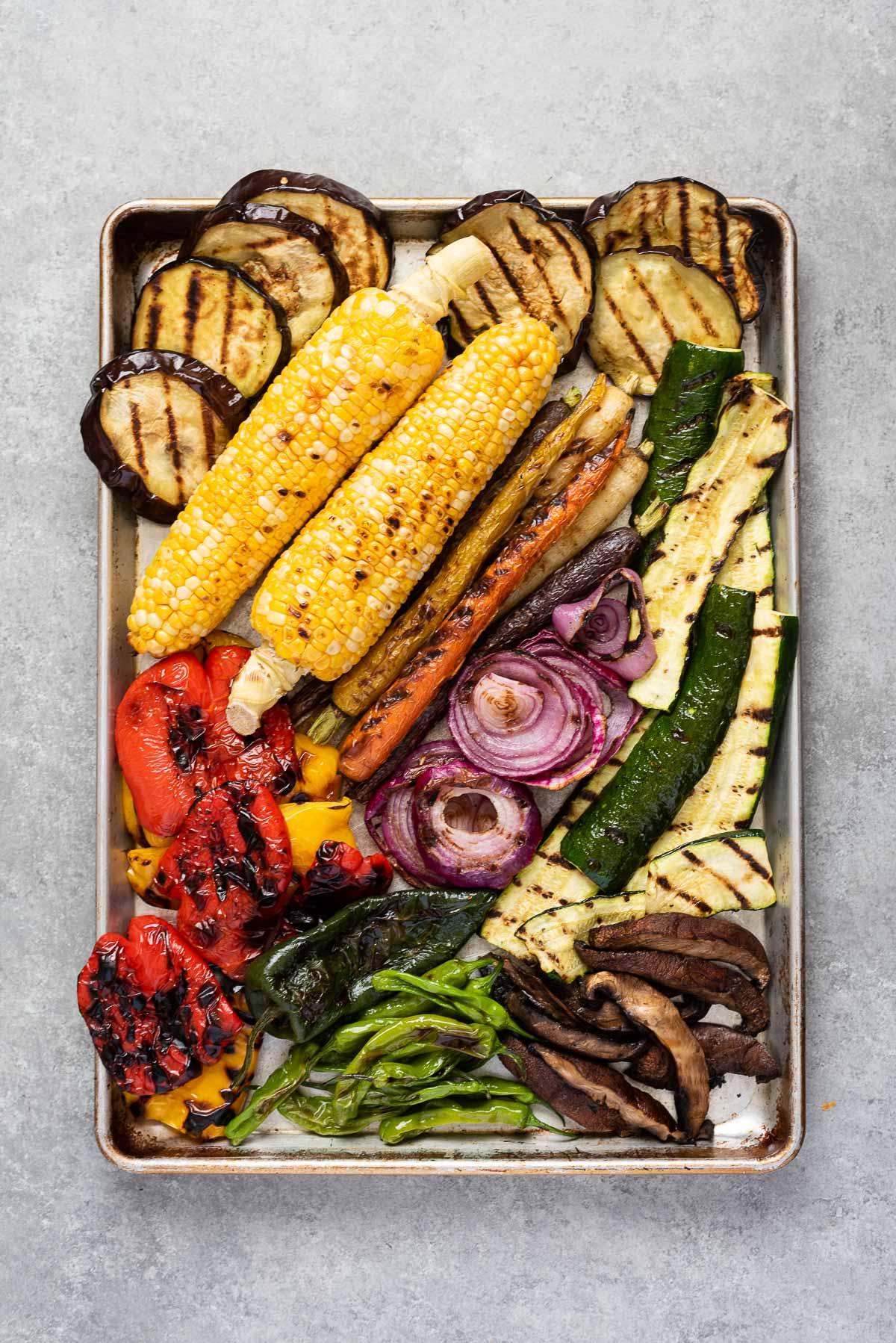 Rimmed baking sheet filled with grilled vegetables