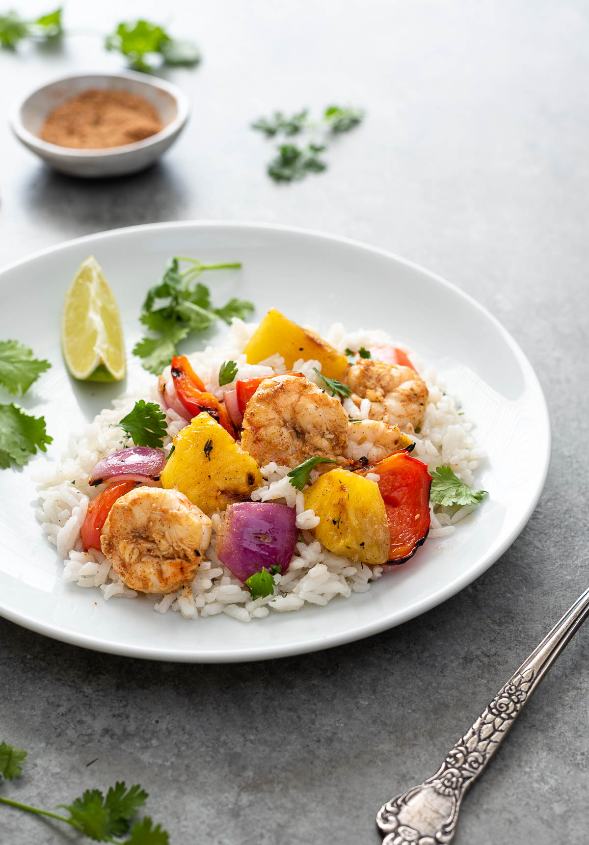 serving of pineapple shrimp skewers over rice on a white plate