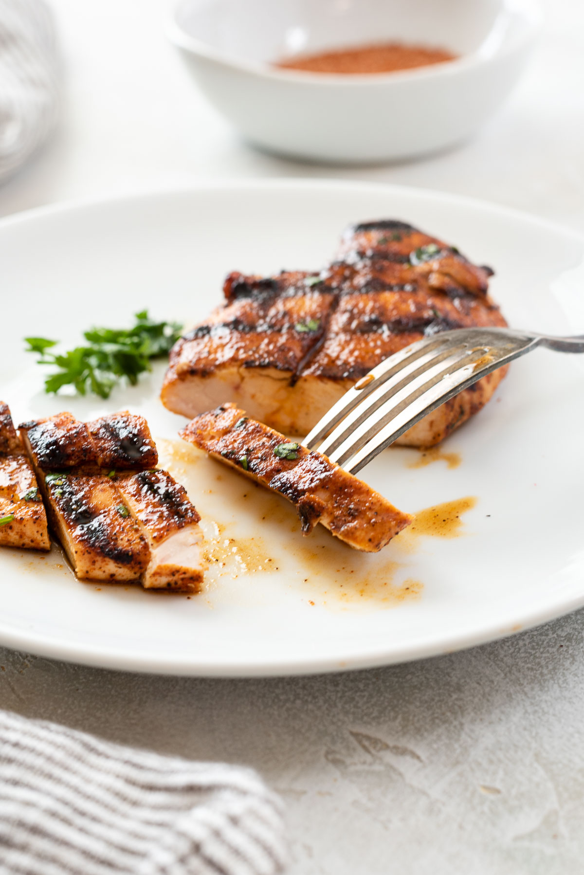 Slice of grilled chicken with bbq rub on fork