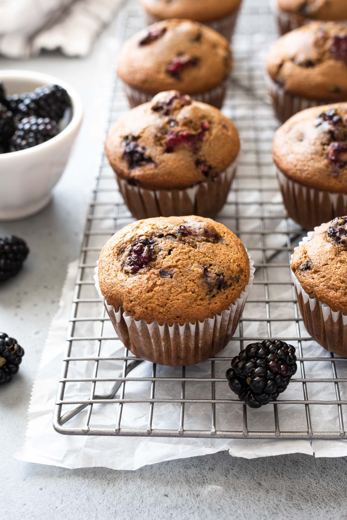 Blackberry muffins on wire rack with fresh blackberries
