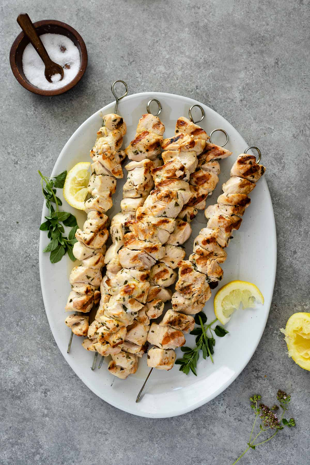 platter of Greek chicken souvlaki with lemon and fresh oregano